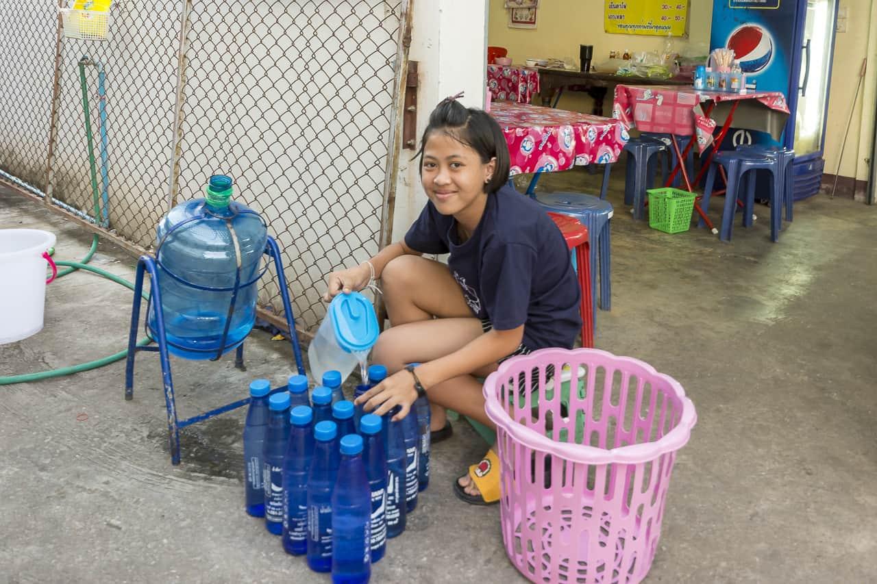 Mädchen beim Abfüllen von Wasser als kleiner zuverdienst