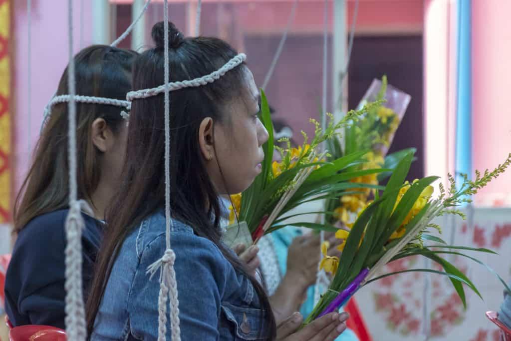 Gläubige die Orchideen beim beten halten