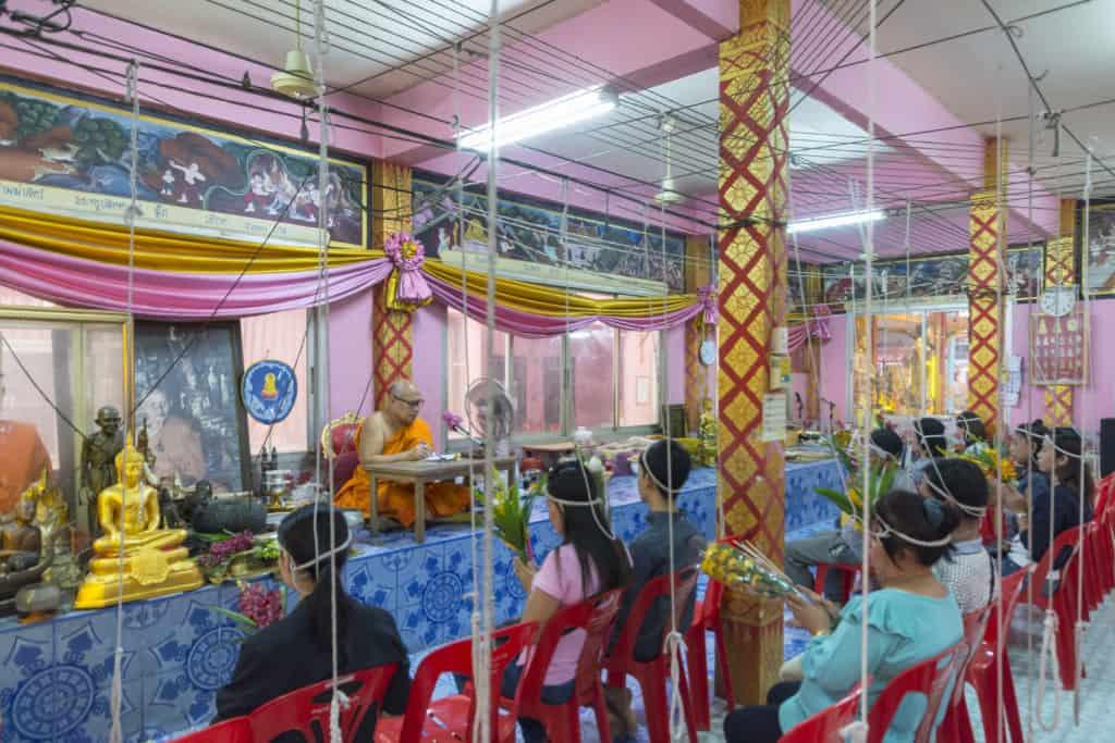 Schnüre verbinden die Gläubigen mit dem Mönch und der Buddhafigur