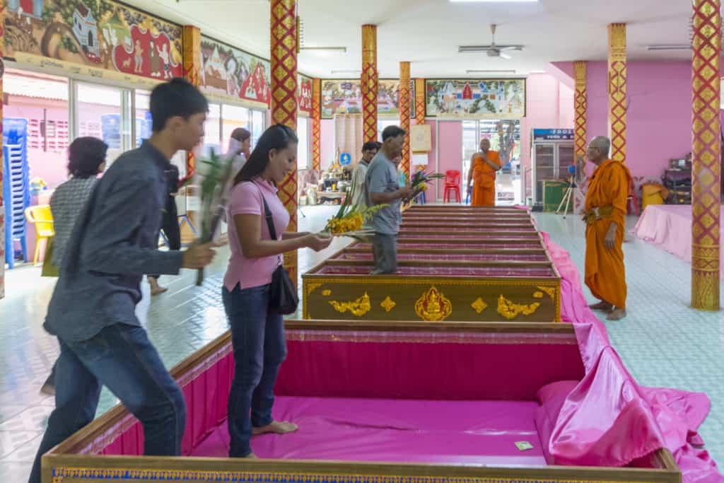 Die ersten Gläubigen besteigen den mit rosa Stoff ausgeschlagenen Zeremoniensarg