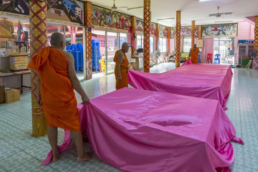 Mönche ziehen das Tuch über den Neugeborenen Buddhisten weg.