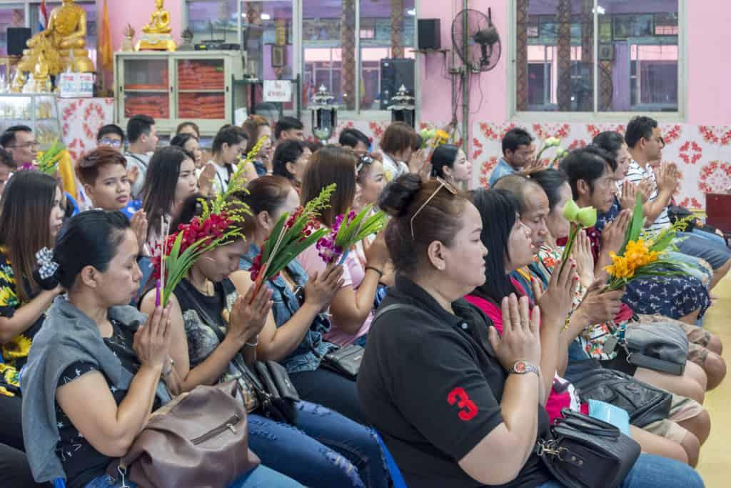 Betende Buddhisten mit Blumen in den Händen im Wat Ta Kien