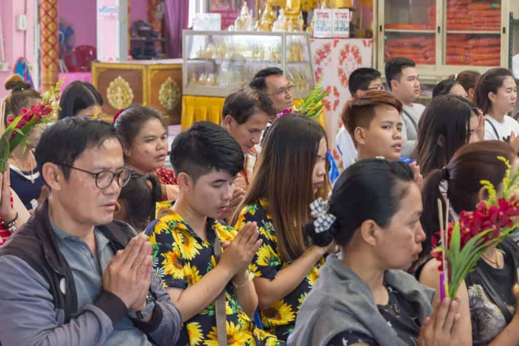Betende Buddhisten mit Blumen in den Händen
