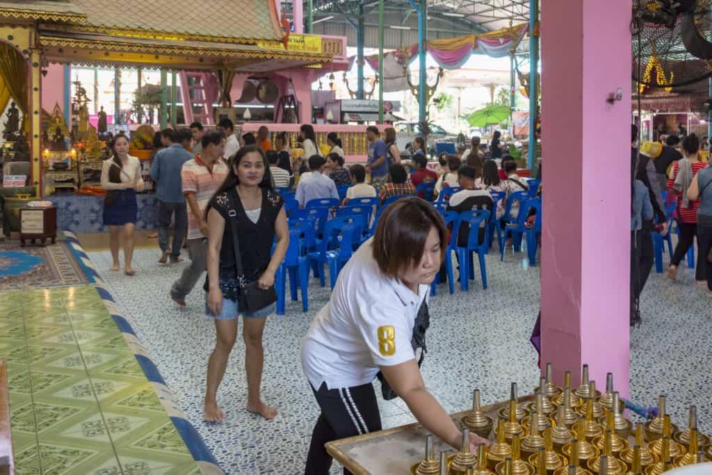 Die Gläubigen Buddhisten geben Spenden bei den Mönchen ab.
