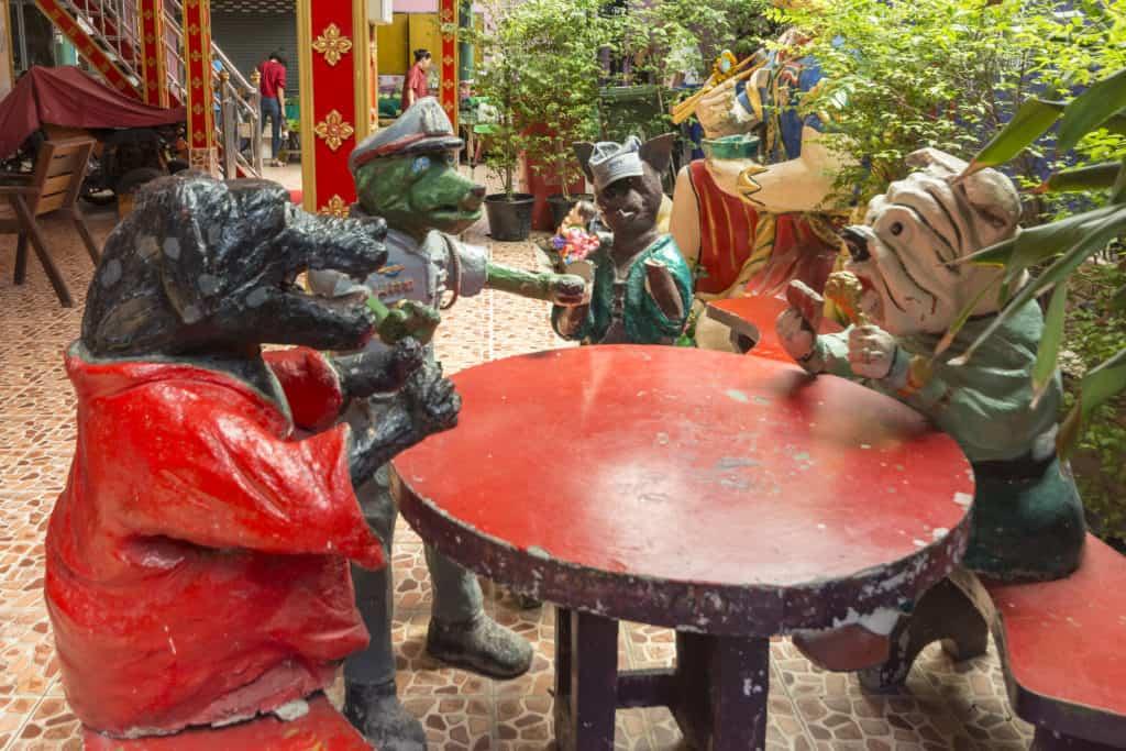 Merkwürdige Figuren aus Beton beim Kartenspielen