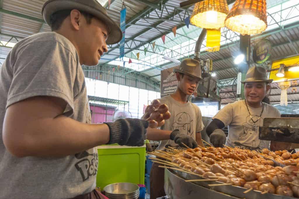 Sticks mit Ping Pong food , kleinen Fleischkugeln aus dem sich drehenden Grill am floating market