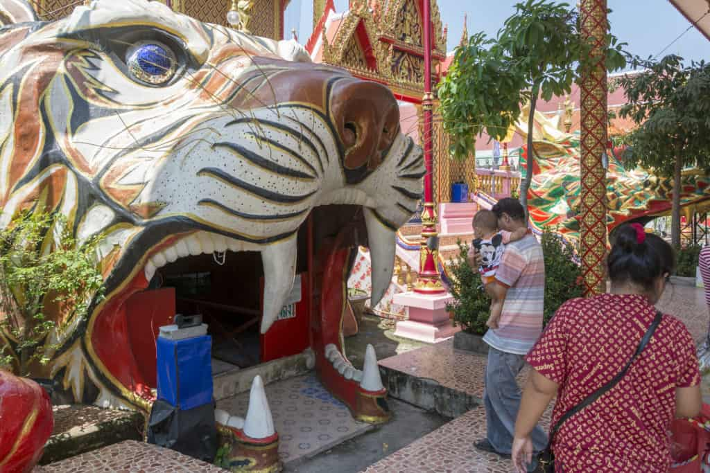 Familie betritt durch den Tigerkopf das Kellergewölbe im Wat Ta Kien