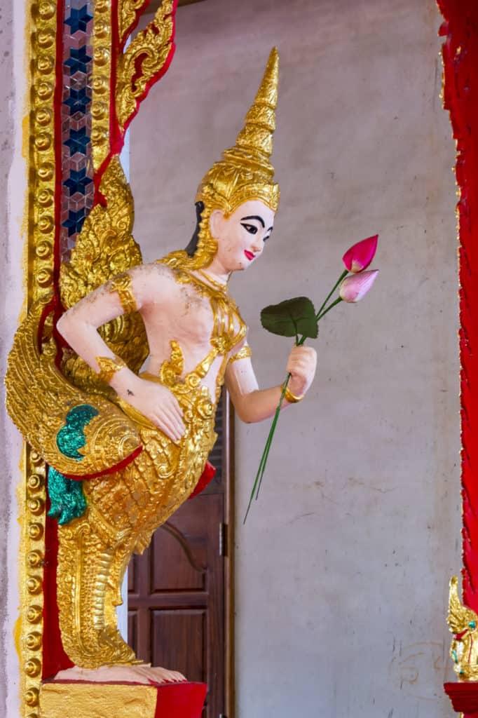 Weibliche Kinnara übergibt Buddha Lotusstengel