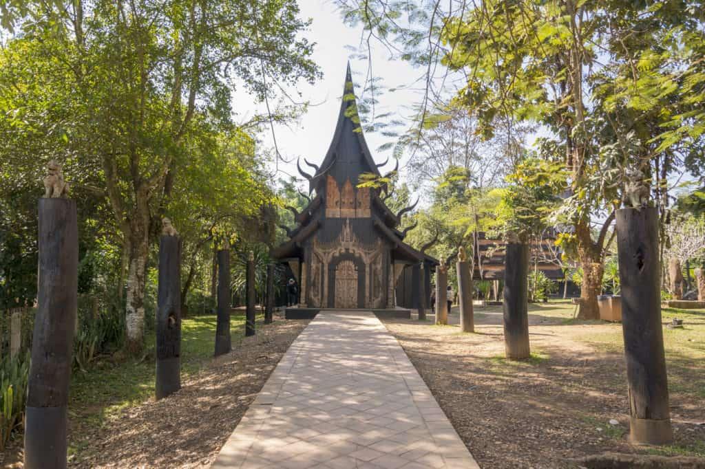 Holzhaus mit Zügen eines Tempels und den Weg gesäumt mit Tierfiguren auf Holzstämmen