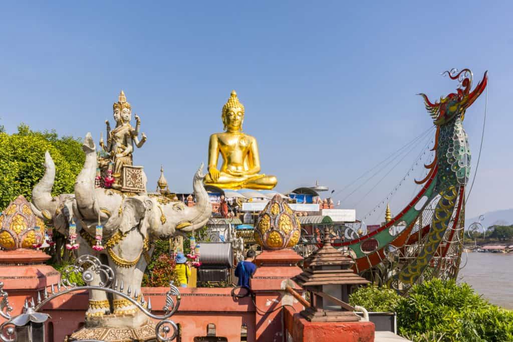 Farbenfroher Tempel mit goldenem Buddha am Mekong im Goldenen Dreieck