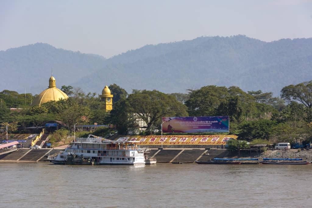 Tribüne am Ufer des Mekongs in Laos mit Uhrenturm und Tempelkuppel