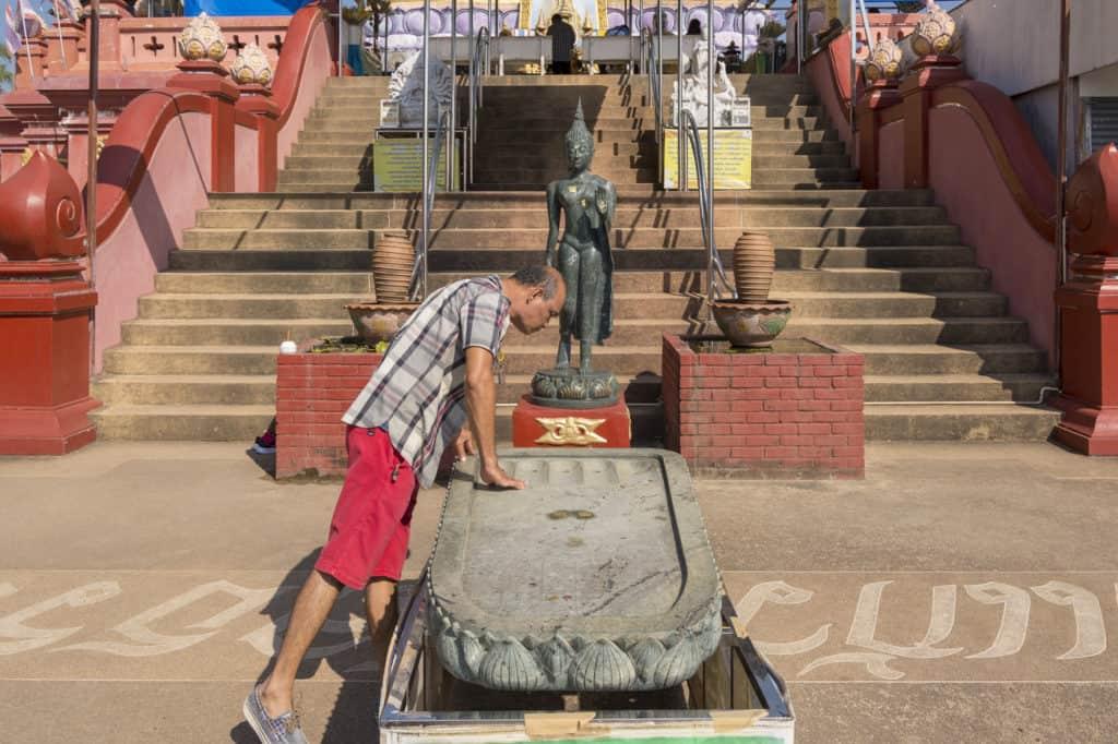 Ein Mann beugt sich über den Fußabdruck von Buddha dessen Berührung Glück bringen soll