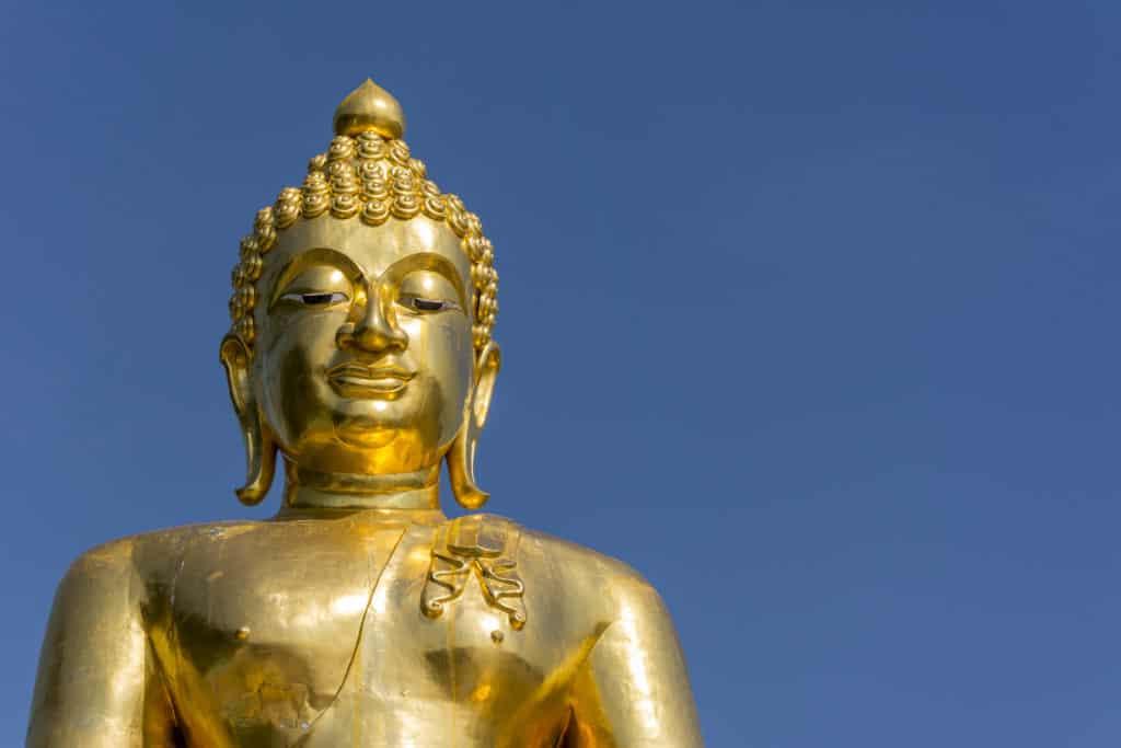 Die goldene Buddha Statue leuchtet im blauen Himmel am Goldenen Dreieck in Thailand
