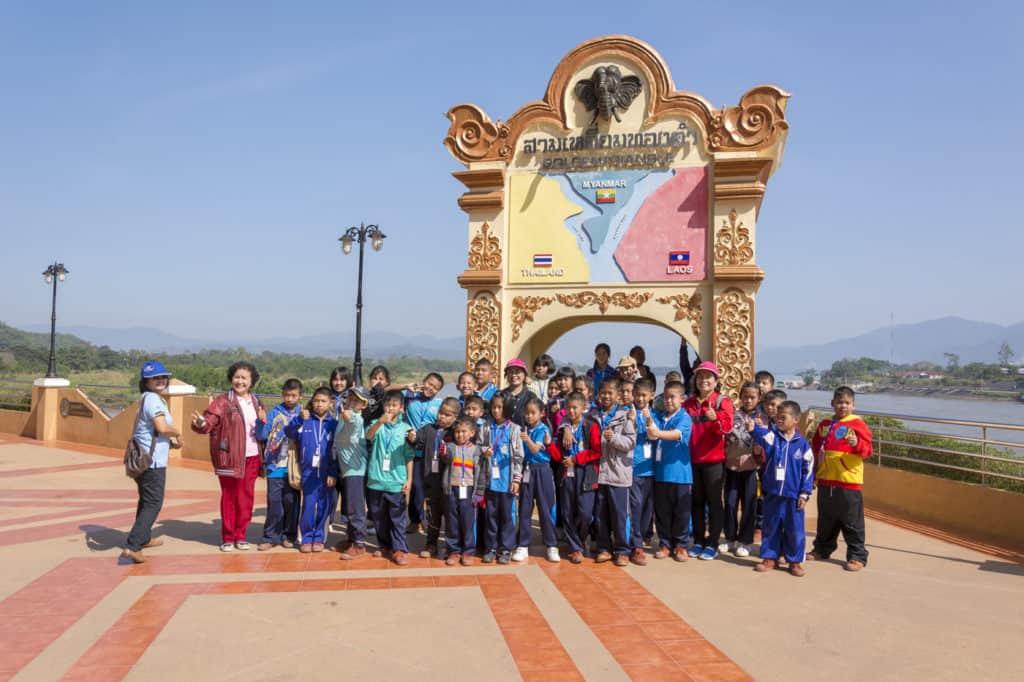 Thailändische Schulklasse mit Torbogen am Goldenen Dreieck in Nordthailand