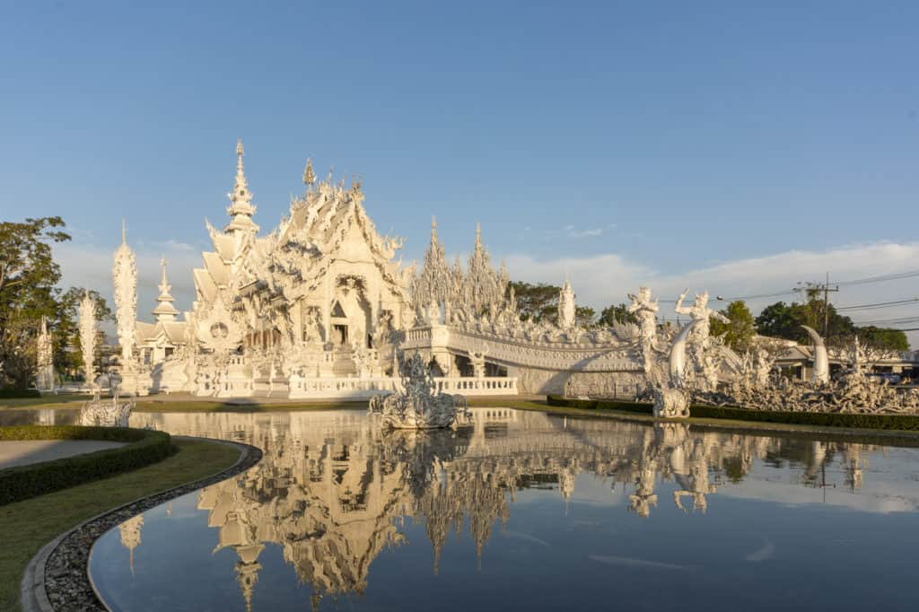 Der Weiße Tempel in Chiang Rai im Morgenlich spiegelt sich im Wasser - Wat Rong Khun