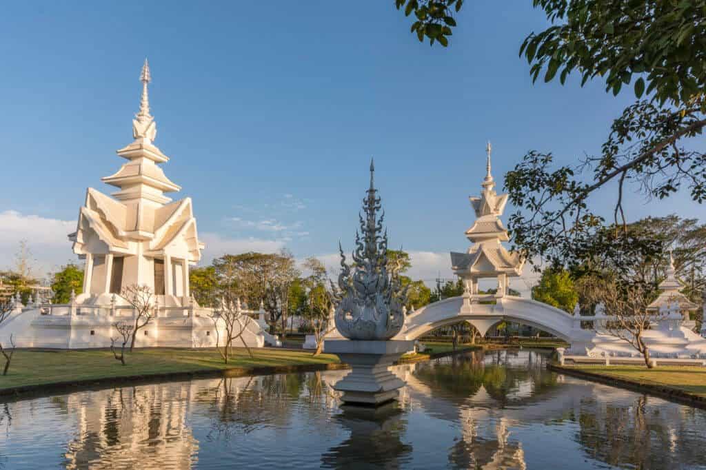 Die Sukhawadee Brücke mit dem Buddhis tower spiegeln sich im Wasser - Wat Rong Khun