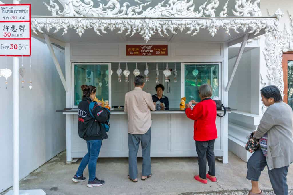 weißer kleiner Verkaufsstand der mit den Einnahmen zum Erhalt und Ausbau des Tempels - Wat Rong Khun beiträgt mit kaufwilligen Touristen