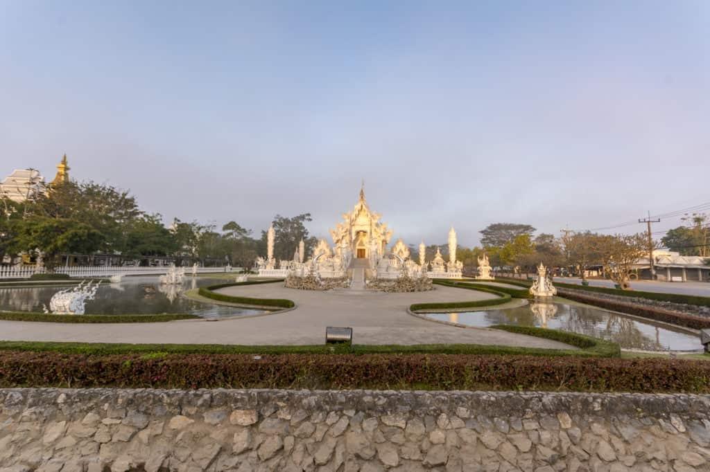 Ins morgendliche Sonnenlicht getaucht strahlt der Weiße Tempel in Chiang Rai