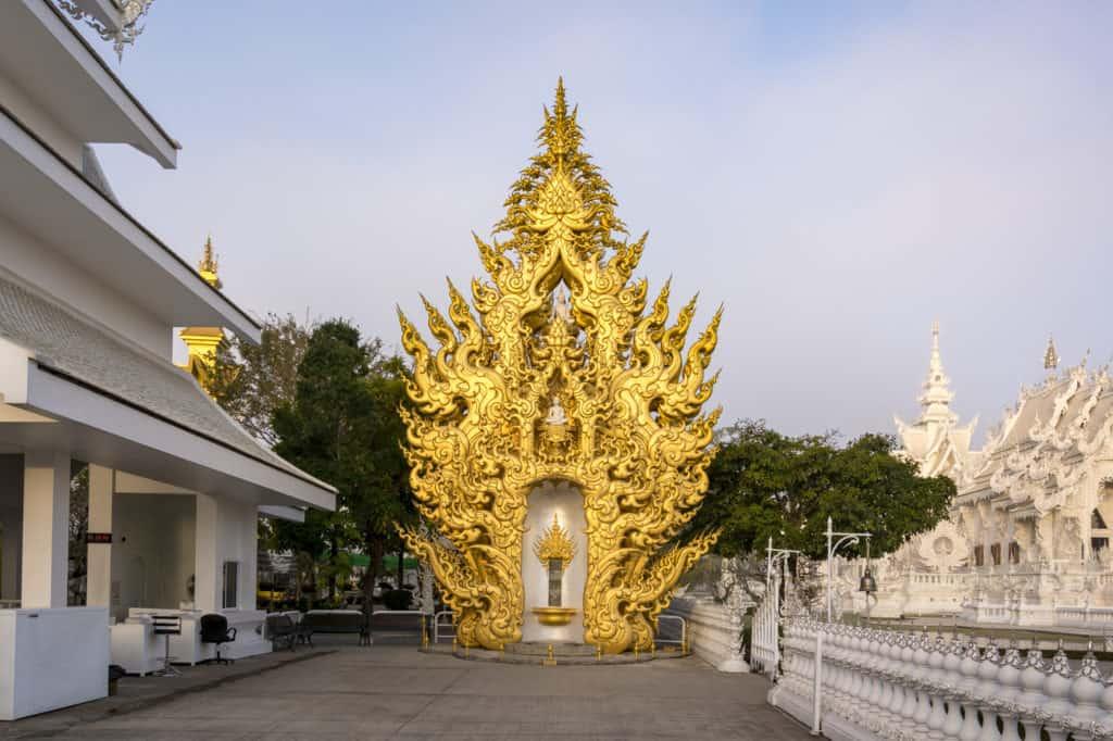 Ganz in Gold gehalten wirkt der Buddha Relics Tower vor dem blauen Himmel im Weißen Tempel beeindruckend.