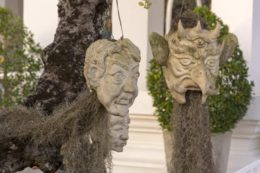 Steinmasken an einem Baum als Sinnbild der vielen Verstorbenen Seelen im Weißen Tempel von Chiang Rai