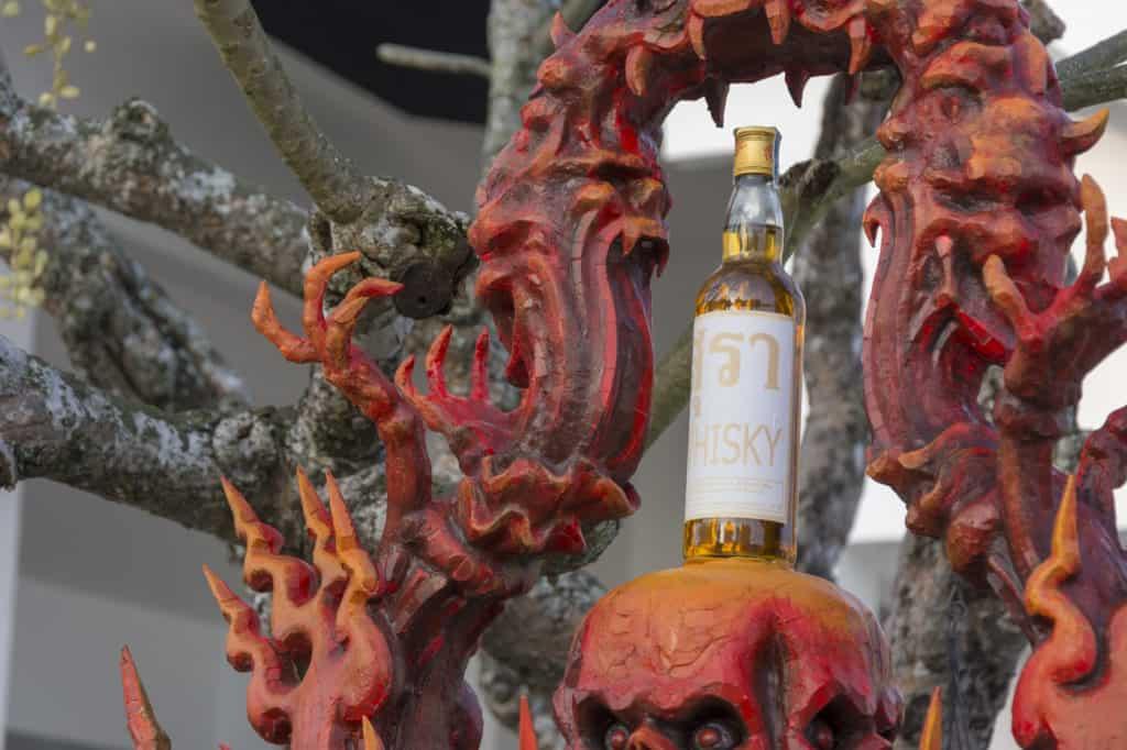 Eine Flasche auf dem Totenkopf symbolisiert den Zusammenhang zwischen Alkohol und dem Tod
