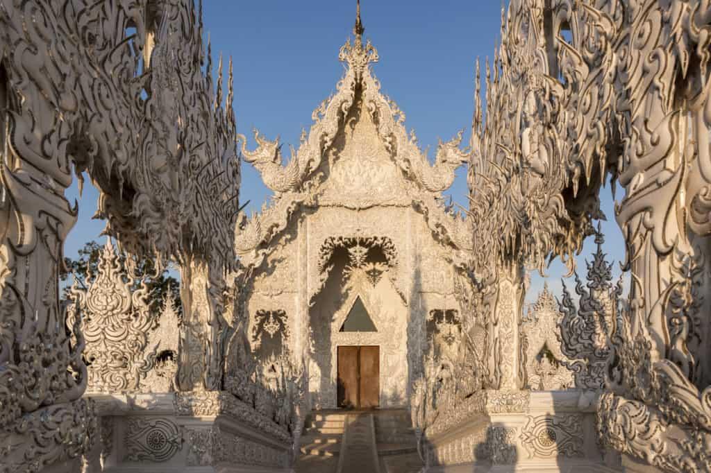 Eingangsbereich des Weißen Tempel in Chiang Rai im Morgenlicht.