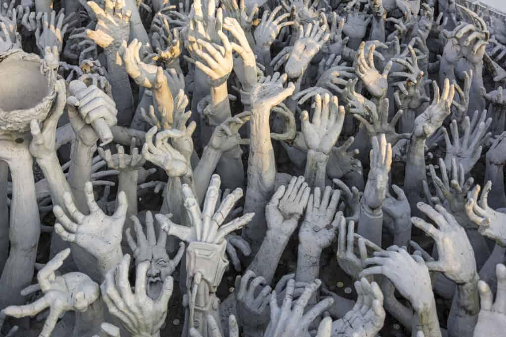 Hände aus Stein strecken sich aus der Hölle im Weißen Tempel von Chiang Rai in die Richtung Himmel