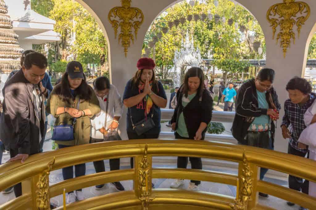 Menschen werfen Münzen in den goldenen Wunschbrunnen