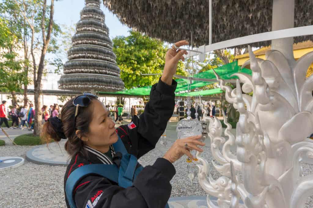 Thailänderin hängt eine Plakette an dem kunstvoll gestaltetem Turm im Weißen Tempel von Chiang Rai auf