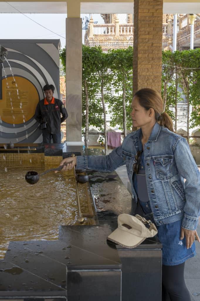 Junge Thailändische Frau fängt das heilige Wasser eines Brunnens auf