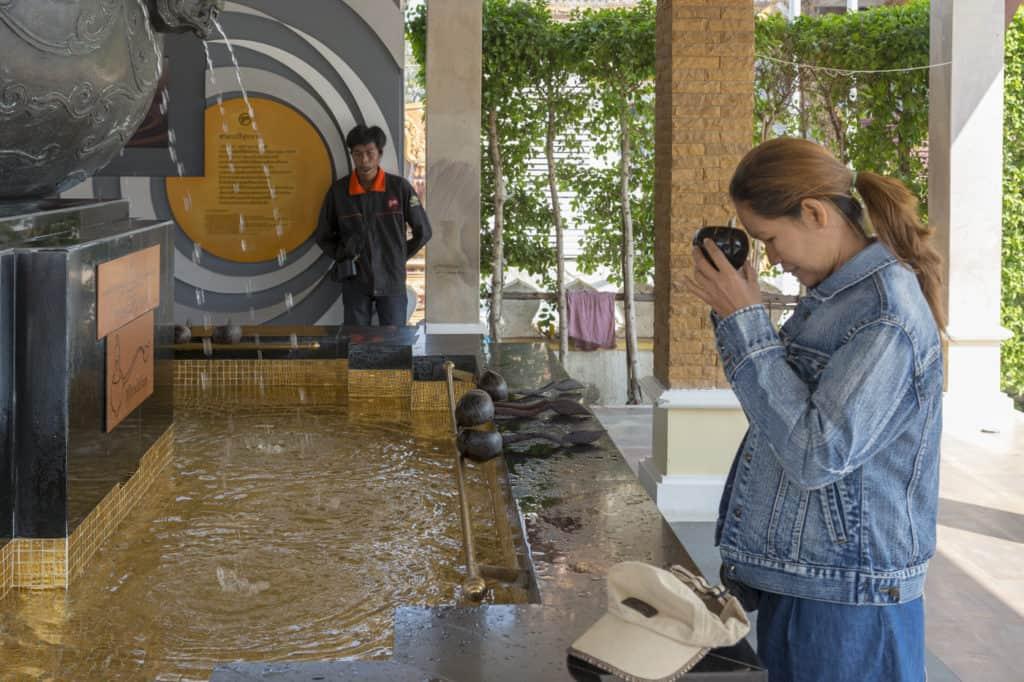 Thailänderin betet mit dem heiligen Wasser vor der Stirn
