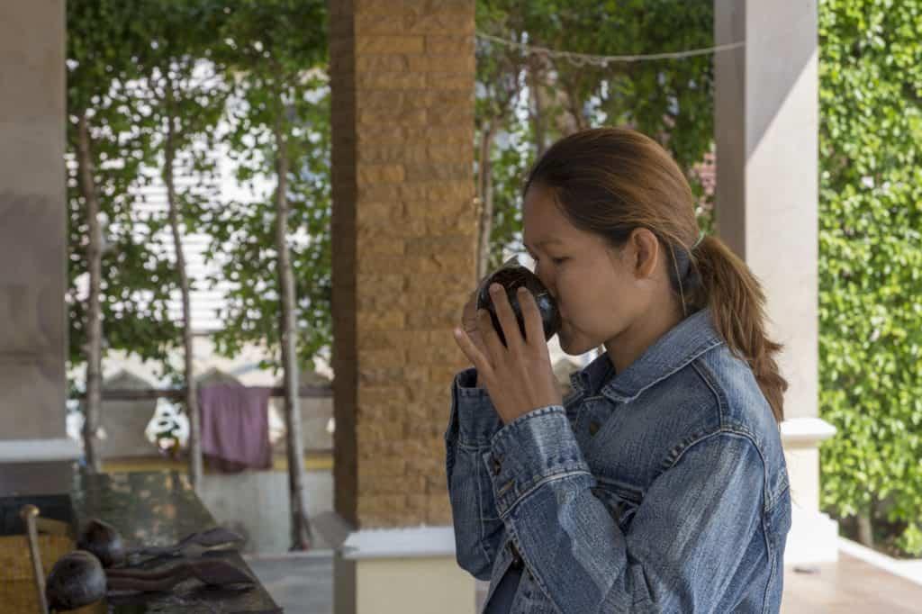 Thailänderin trinkt das heilige Wasser aus der Schöpfkelle