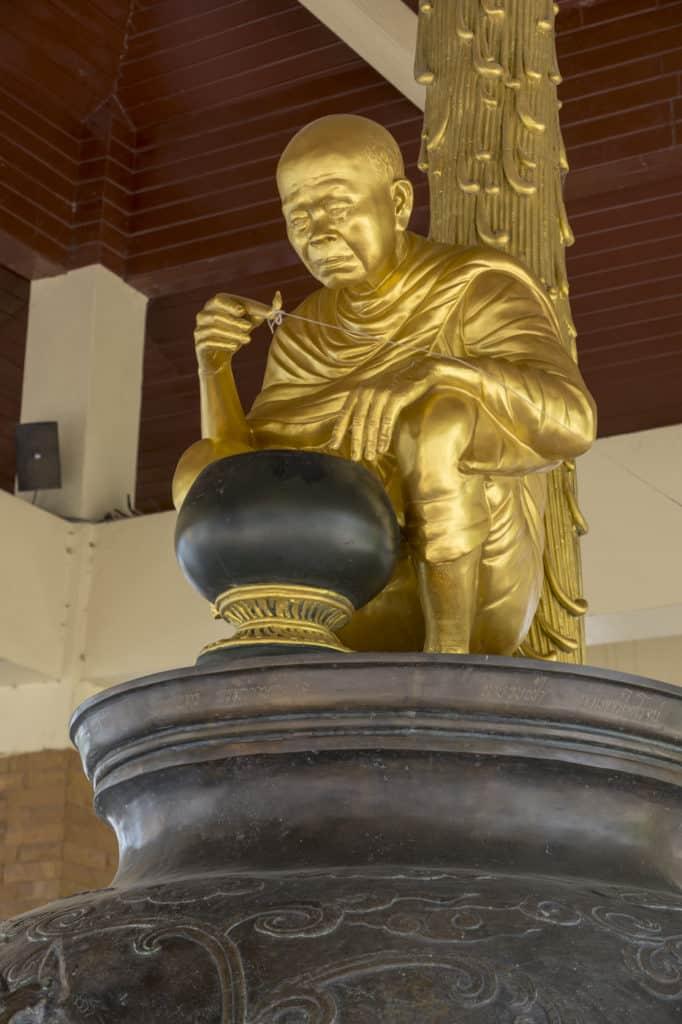 Die Statue des ehrwürdigenLuang Phoo Khoo Prisuddho beobachtet die Szenerie der wassertrinkenden Frau