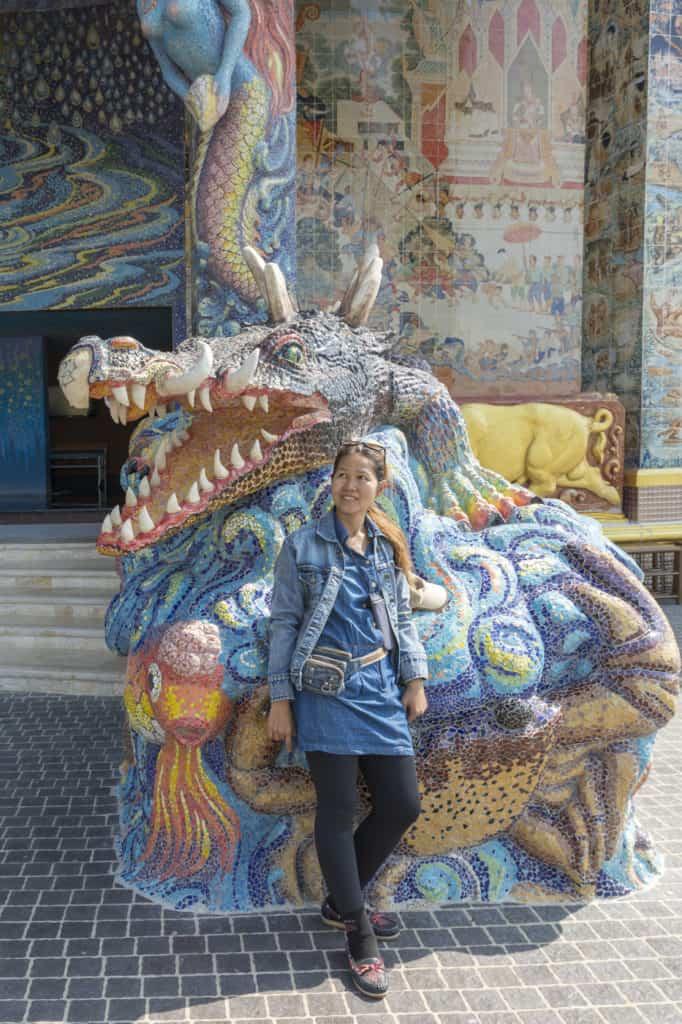 Thailänderin vor einem imposantem Drachen als Größenvergleich im Wat Ban Rai in Thailand