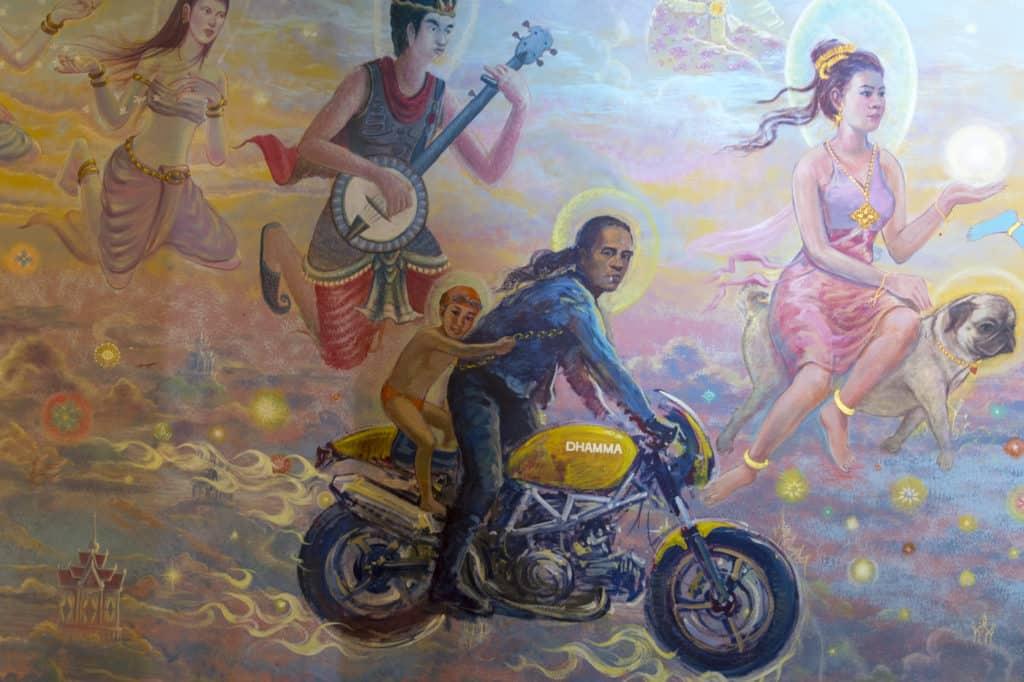Wandgemälde im Tempel Wat Ban Rai, Motorradfahrer mit Kind, ohne Helm dafür auf einer schweren Maschine Namens Dharma.