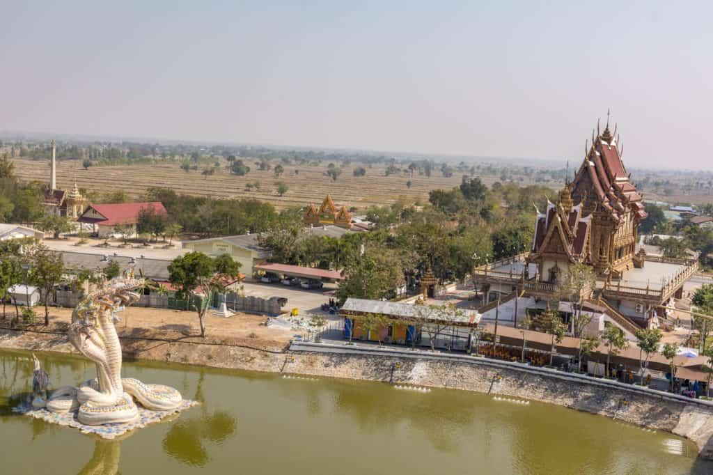 Blick über die Ebene im Isaan mit der Naga Schlange und dem Bot des Wat Ban Rai in Thailand