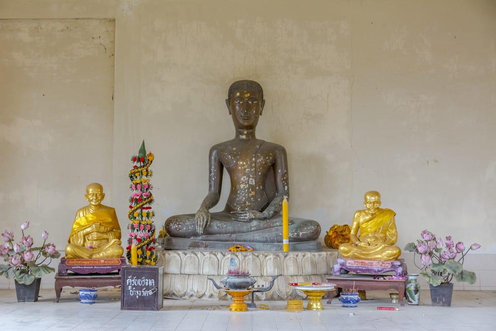 Buddha-Figur im Lotussitz mit überproportionalem Kopf