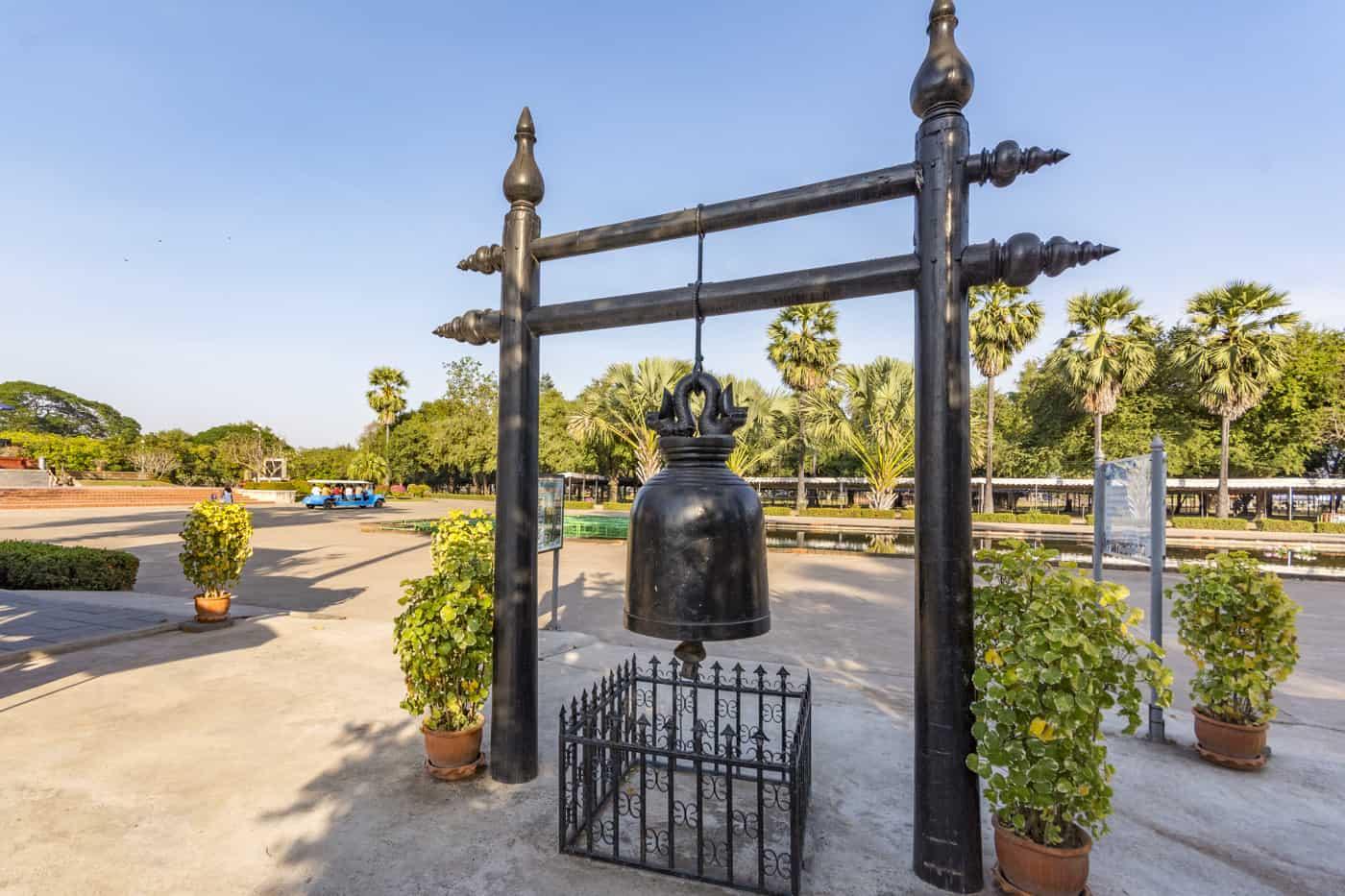 Eine Bronze Glocke hängt am Gerüst und ist die Nachbildung der Ramkhamhaeng Glocke
