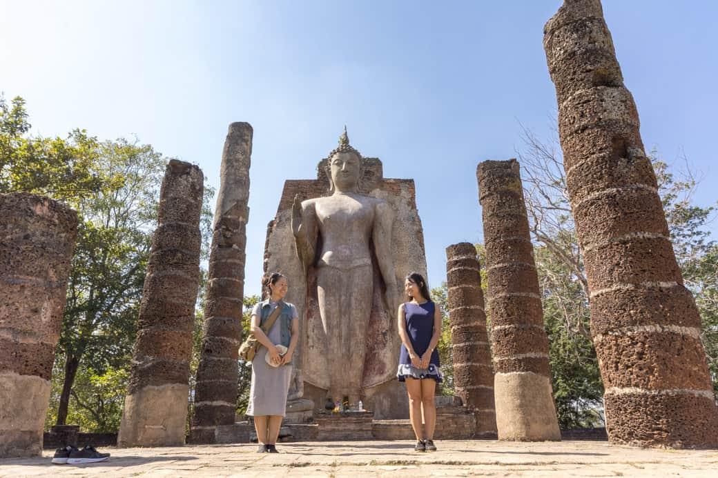 Zwei junge Thaifrauen vor dem aufrecht sthenden Bhudda im Wat SaPhan Hin