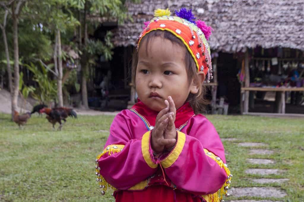 Kleines thailändisches Kind lernt füh die Erwachsenen mit einem Wai zu begrüßen