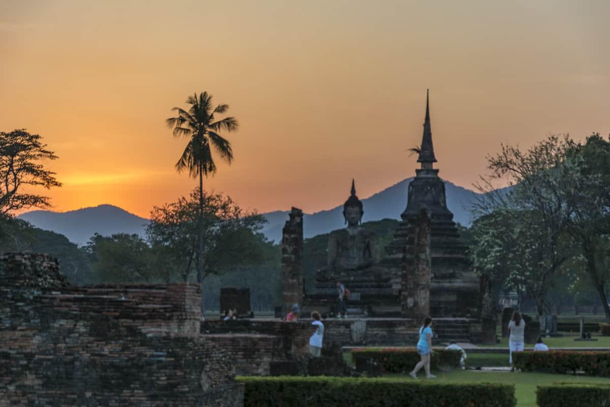 Wat Mahatat im historical park Sukhothai im Sonnenuntergang mit Bergkette und Palmen im Hintergrund - Thailand