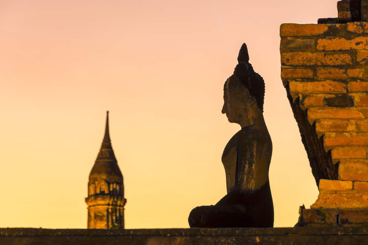 Buddha-Figur im Gegenlich beim Sonnenuntergang im Wat Mahatat im historical park Sokhothai