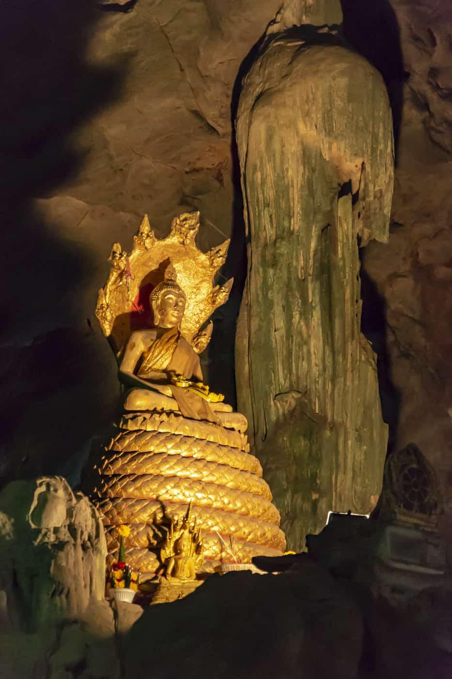 Goldener Buddha neben Stalakmiten und Stalagtiten in der Khao Luang Höhle in Phetchaburi Thailand