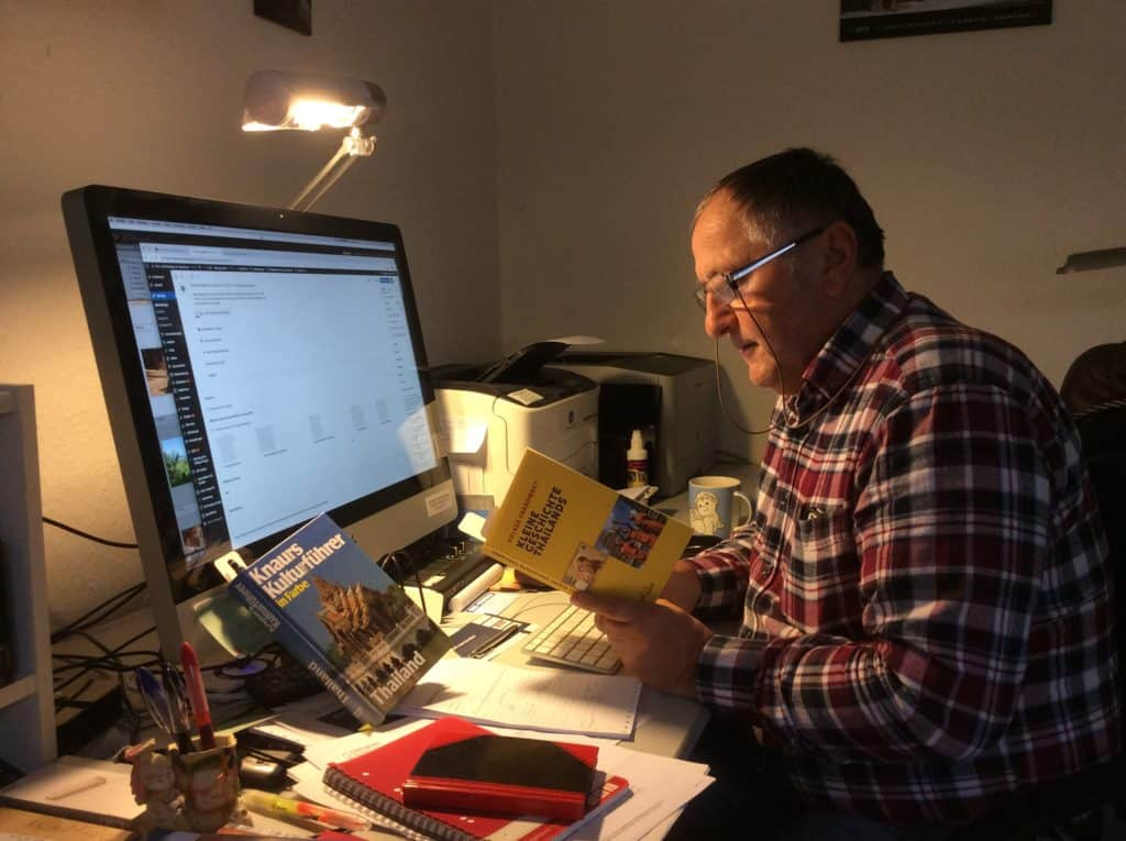 Reiner Kerner mit Buch am Computer bei der Reiseplanung