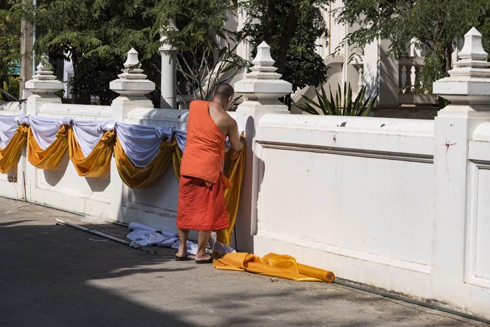 Mönch bringt im Wat Mahatat Girlanden an