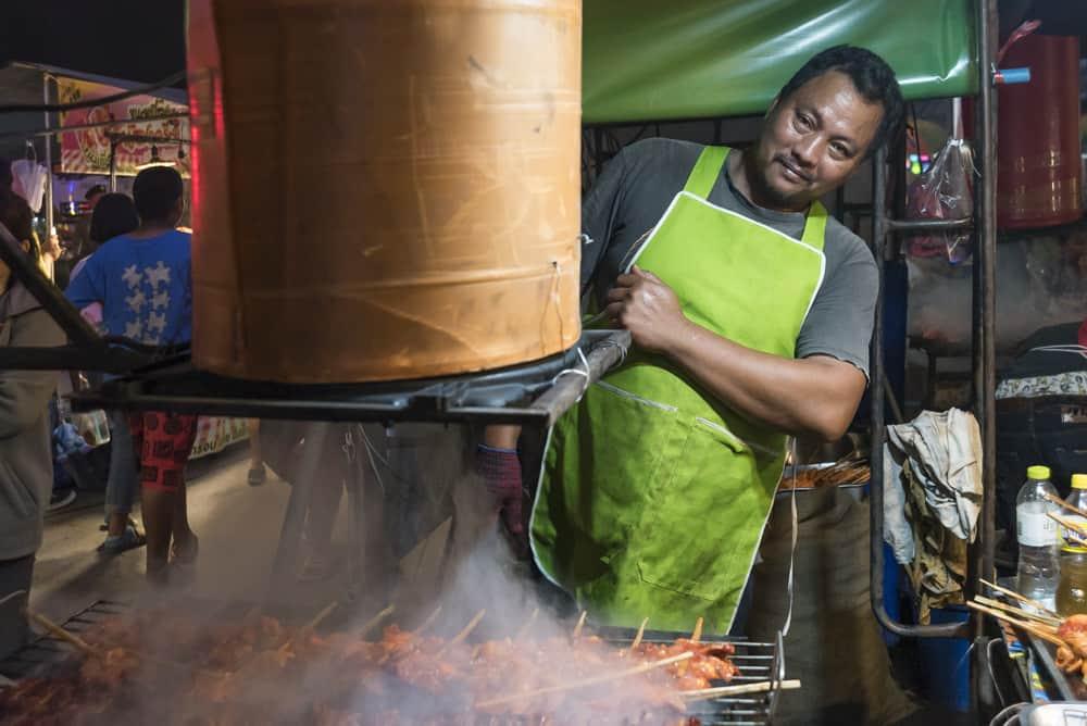 Mann beim Grillen von Fleischspießen mit besonderer Absaugung