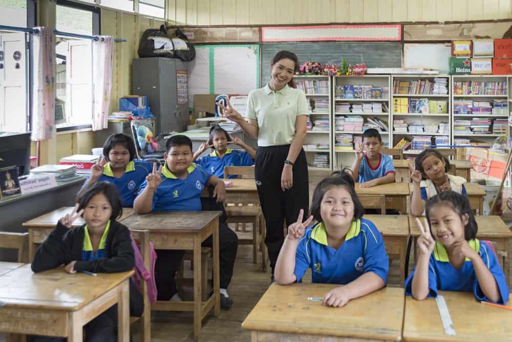 Winkende Kinder mit Lehrerin einer thailändischen Schule