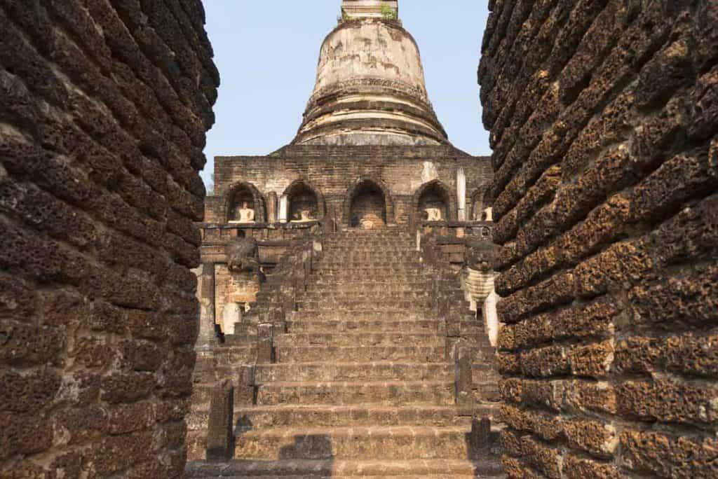 Durchblick beim Tor der zweiten Mauer auf die Treppen des Chedis im Wat Chang Lom in Si Satchanalai