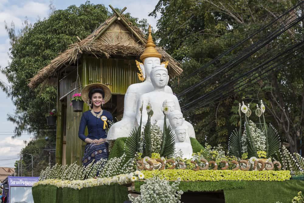 Junge Thailänderin auf dem Festwagen mit Buddha-Figuren