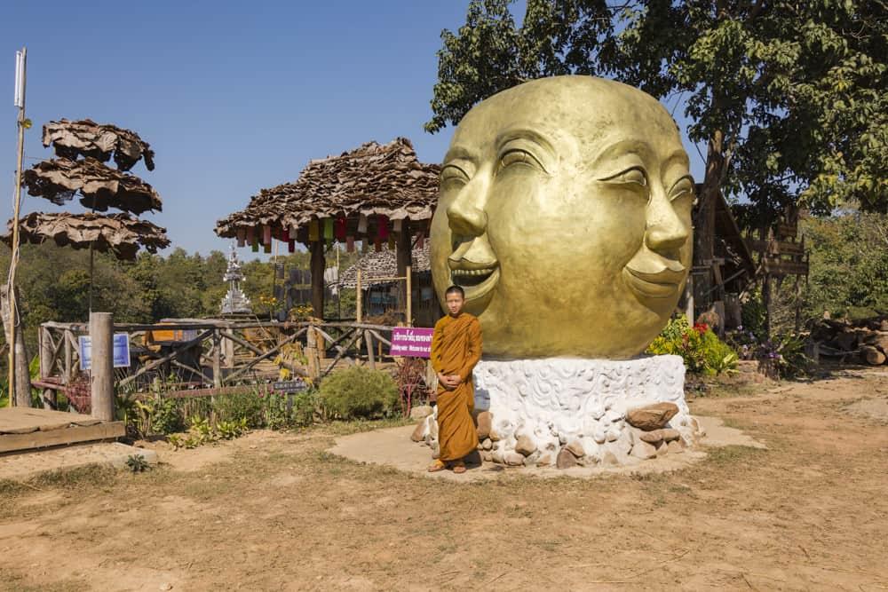 Junger Mönch steht vor einem besonderen Buddha-Kopf - Bambus-Brücke
